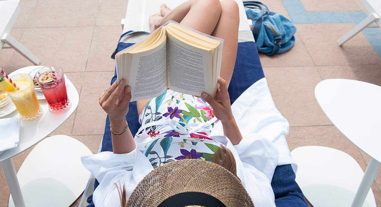 A guest reading a book at Hotel Excelsior Venice Lido Resort